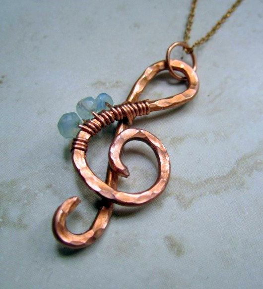 Copper wire treble clef necklace hammered (flattens out wire for strength) and textured (indents - using texture hammer), polished to a high shine. A few beads then wire wrapped around the clef.