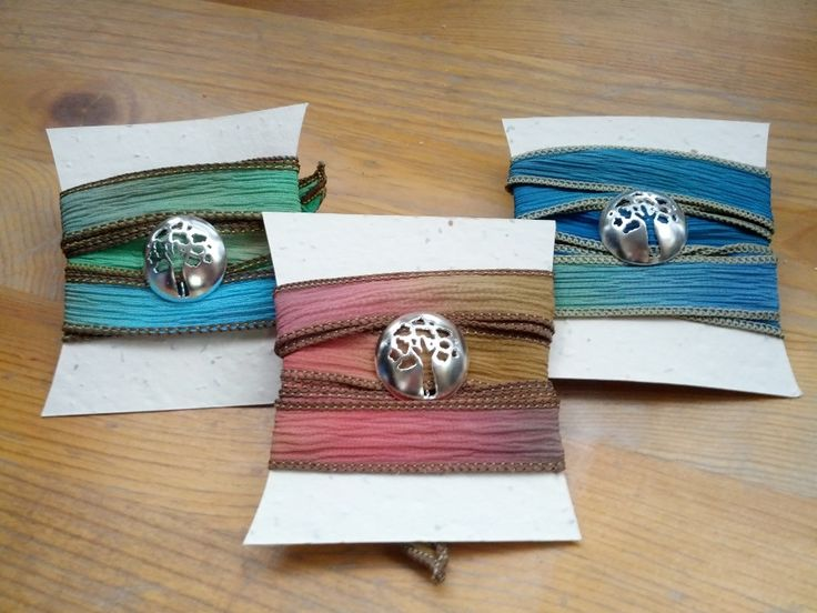 """Tree of Life bracelets by Slashpile Designs. The tree silhouette is pierced from a 1"""" diameter sterling silver dome, and comes on a silk ribbon from made from re-purposed saris."""