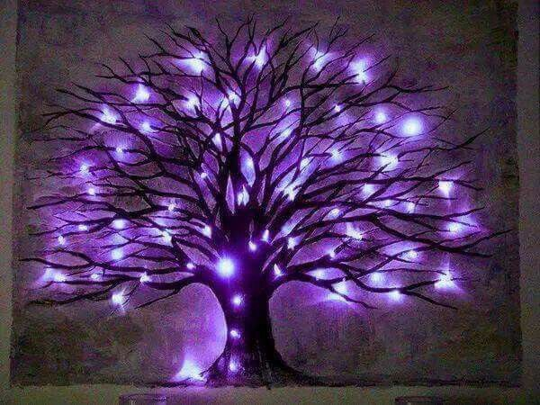 A TREE LIGHTED BY PURPLE LIGHTS.