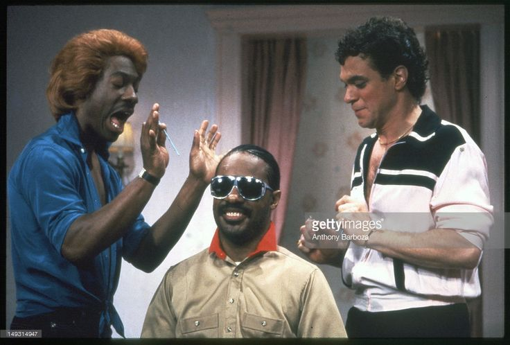 American comedians Eddie Murphy (left), in costume as the character Dion, and Joe Piscopo (right), in costume as the character Blaine, perform a skit with musician Stevie Wonder on an episode of the television show 'Saturday Night Live,' New York, New York, 1983.