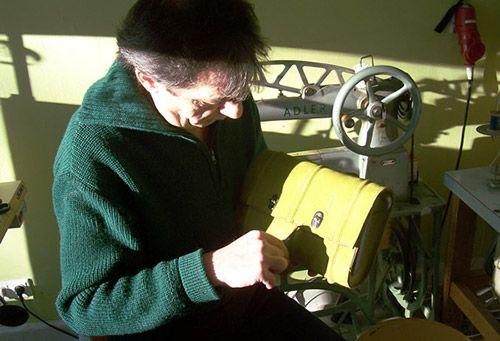 Qualitätsprüfung an der fertig gestellten Ledertasche, im Hintergrund die Adler Nähmaschine