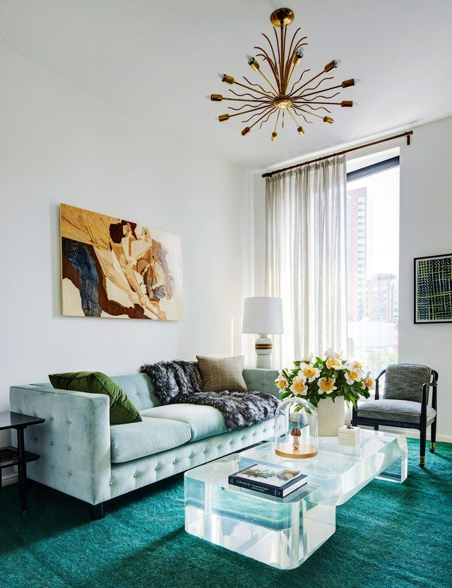A glamorous living room featuring a vintage Karl Springer cocktail table and a vintage brass chandelier | archdigest.com