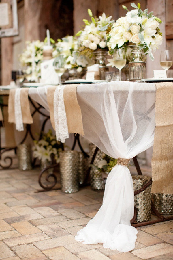 Sheer fabric tied at opposite corners, with burlap runners and lace napkins