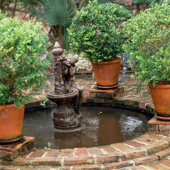 Victorian Appeal for Your Fountain - Statues can provide the perfect base for your outdoor fountain. This fountain boasts a weathered metal statue of a woman clinging to an ornate obelisk, giving the fountain a Victorian appeal. Terra-cotta pots filled with small-leaf boxwood surround the round brick basin. Create symmetry with a focused pattern, such as the multitude of circles that highlight this design.