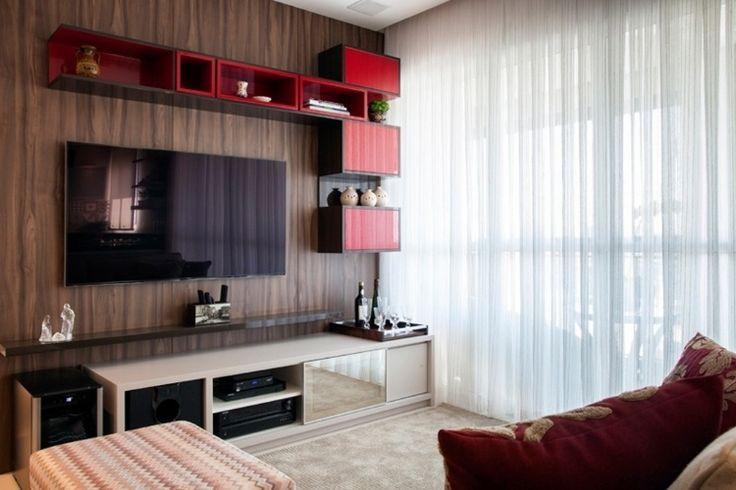 Na proposta do escritório Escala Arquitetura e Construção, o painel amadeirado dá elegância ao espaço de TV e distingue-se pelos nichos e armários com detalhes em vermelho, que emolduram o aparelho. O rack branco, que comporta os equipamentos do home theater, é leve e combina com o tapete
