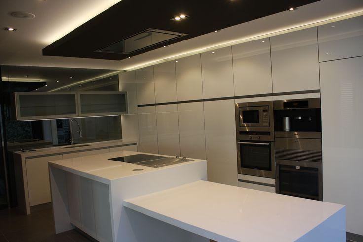 Proyecto de Carlos Sancho. Office Hogar. Cocina blanca con zona de columnas de almacenaje y gran isla.
