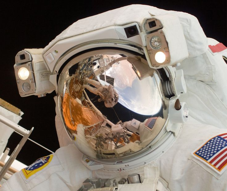In this close-up scene featuring astronaut John Grunsfeld performing a spacewalk to work on the Hubble Space Telescope, the reflection in his helmet visor shows astronaut Andrew Feustel taking the photo as he is perched on the end of the Canadian-built remote manipulator system arm. (NASA)