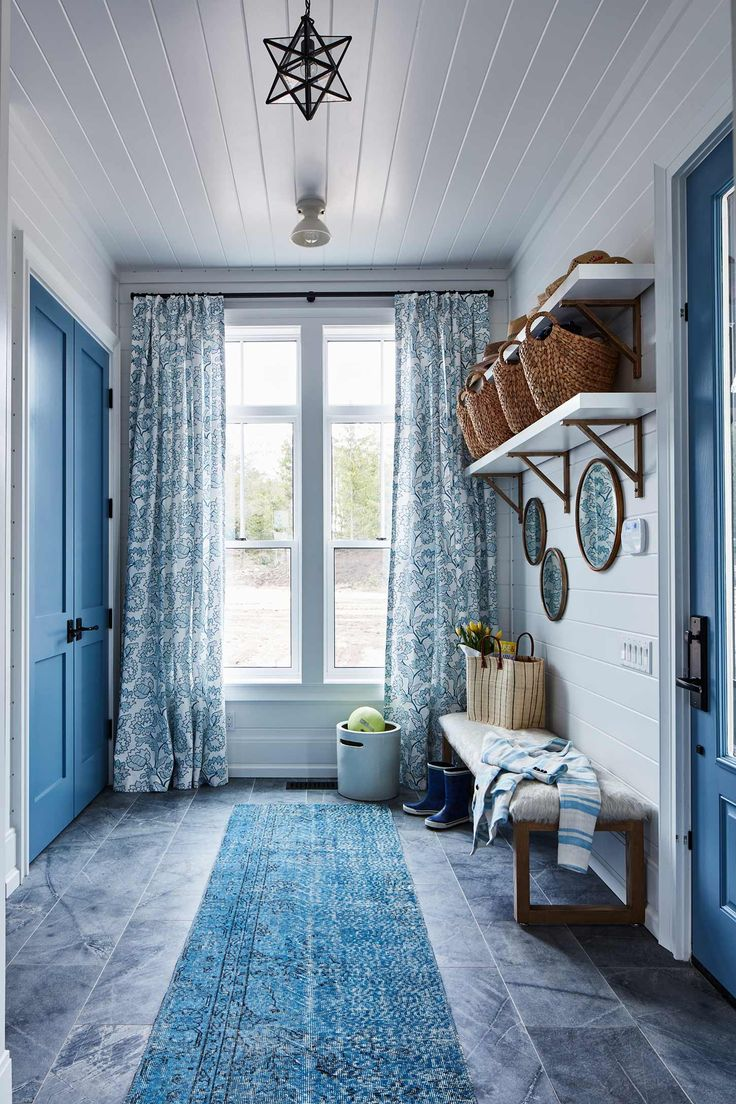 A mudroom clad in rich blues and fanciful patterns.