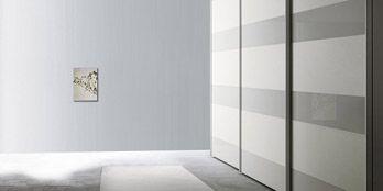 San Giacomo - Armadio Anta Stripe Armadio con anta nel modello Stripe, nella versione scorrevole, caratterizzata dalla lavorazione a fasce orizzontali che permette di accostare differenti finiture. Per le fascie larghe sono disponibili le finiture: materico o materico laccato nei colori a campionario, impiallacciato rovere brown o noce o laccato opaco nei colori a campionario. Le fasce strette sono disponibili in vetro laccato lucido, satinato o Stop Sol riflettente nei colori a campionario.