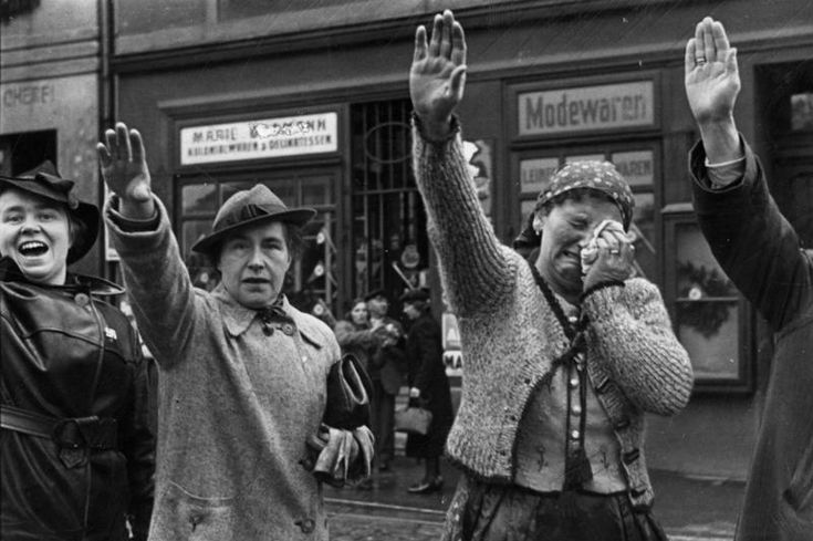 A Sudeten German woman cried in misery as she gave the Nazi Party salute while two others saluted with happiness, Sudetenland, Czechoslovakia, Oct 1938
