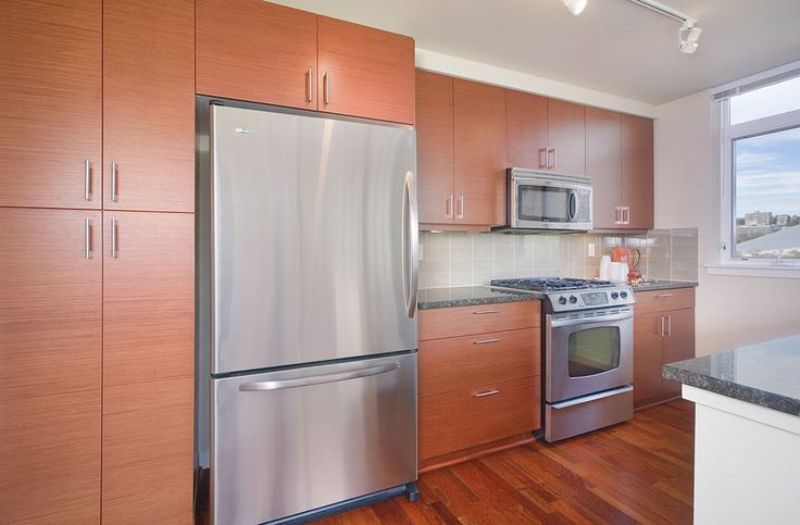 Contemporary kitchen cabinets in horizontal grain, Quartered Cherry Echo Wood veneer with grey subway tile backsplash and stainless steel appliances.