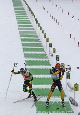 Winner Martin Fourcade of France, left, leaves the shooting range as second placed Arnd Peiffer of Germany shoots in the men's 12.5 km pursuit at the IBU World Cup Biathlon at Khanty-Mansiysk, 2759 km northeast of Moscow, Russia, Saturday, March 17, 2012. (AP Photo/Mikhail Metzel)