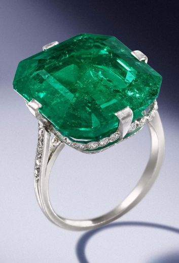 An emerald and diamond ring, by Van Cleef & Arpels, 1920 The octagonal step-cut emerald, weighing 18.67 carats, within a delicate mount millegrain-set with single-cut diamonds and engraved decoration, unsigned, numbered 8752, rubbed French assay mark