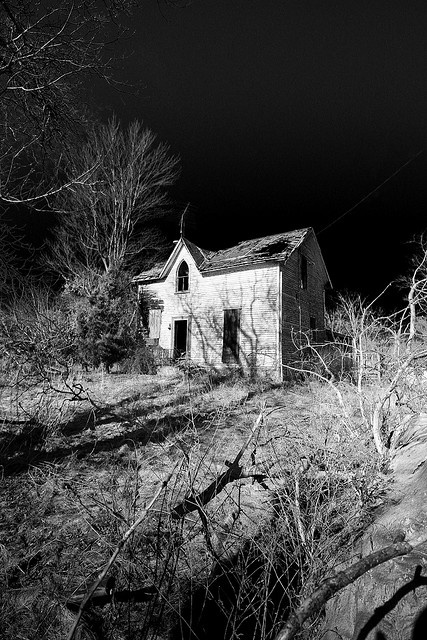 Abandoned, spooky old house. It's haunting secrets safe, beneath the dark, starless, night sky.