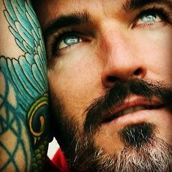 Those tattoos bring out his eyes. Those eyes! Good-looking man. I like the gray in his beard.