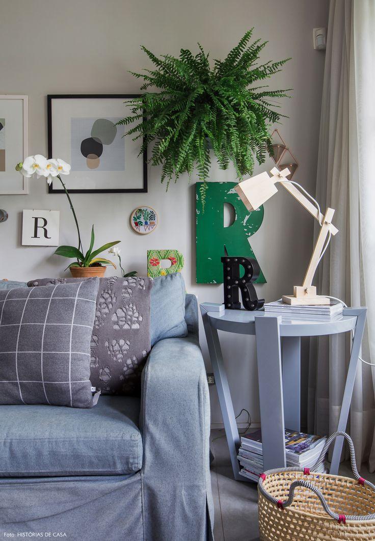 Sofá cinza, mesa lateral redonda e parede galeria com quadros, letras e uma samambaia.