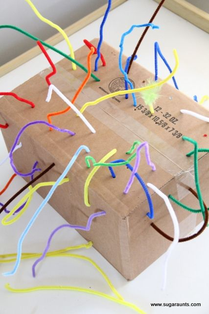Fine motor play with a recycled box and pipe cleaners. This is great for toddlers and preschoolers.
