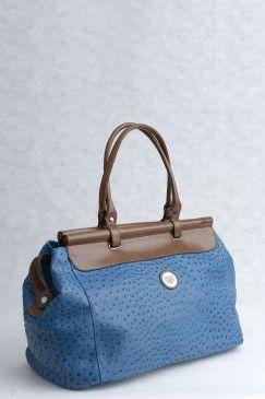 Μαλακή τσάντα ταξιδίου μπλε με καφέ λεπτομέρειες. Δερμάτινη υφή.  Ιδιαίτερο σχέδιο, ξεχωριστό χρώμα, μεγάλη χωρητικότητα.  Εσωτερικά χακί υφασμάτινη φόδρα, ένας ενιαίος μεγάλος χώρος,  λάστοιχο στήριξης του περιεχομένου  και 3 μικρότερες τσέπες (1 με φερμουάρ).