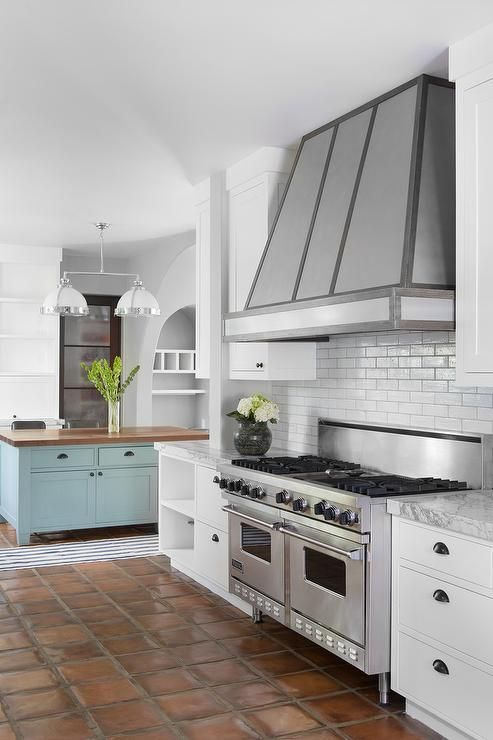 Beautiful kitchen boasts a Restoration Hardware Clemson Classic Double Pendant which hang over a blue kitchen island fitted with end shelves topped with dark stained butcher block alongside a blue striped runner, Dash & Albert Blue Awning Stripe Indoor Outdoor Rug, atop a terracotta tiled floor.