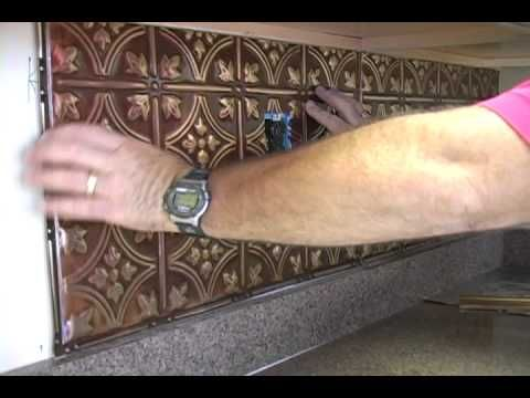 The American Tin Ceiling Company shows the simplicity of installing a tin backsplash for under your cabinets. This tutorial shows the best techniques for turning a boring kitchen into a beautiful place to show off. Easily installed with Liquid Nails, the embossed ceiling tiles are cut and glued to the wall within an hour.