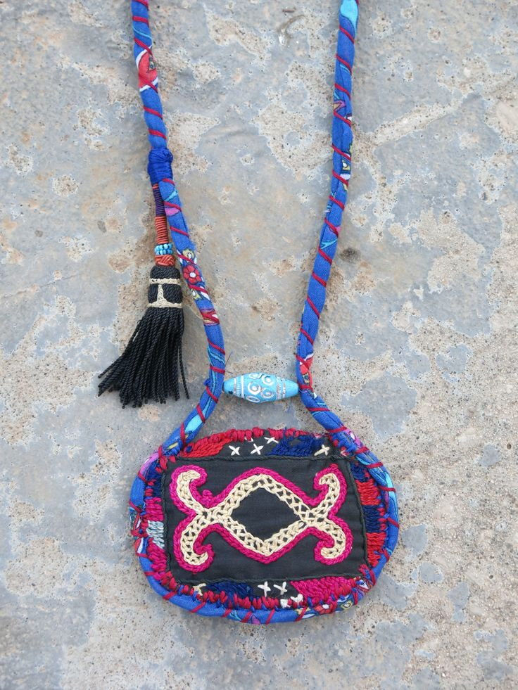 Kinship Stories: Ethnic necklace whose base is made of bohemian Turkish fabric, using a traditional Turkish technique. The fabric centerpiece comes from a vintage Uzbek wall hanging. It is hand-embroidered. The tassel is also vintage Uzbek and it comes from a piece used for hair adornment. The bead, on the other hand, is Egyptian. It is old, wooden and hand-carved and it was found in the Nubia region. This piece is entirely handmade and is a one-of-a-kind item.