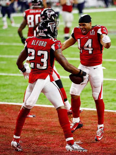 Eric Weems and Devonta Freeman celebrate with Robert Alford of the Atlanta Falcons after Alford scored a touchdown on a 82 yard interception against...