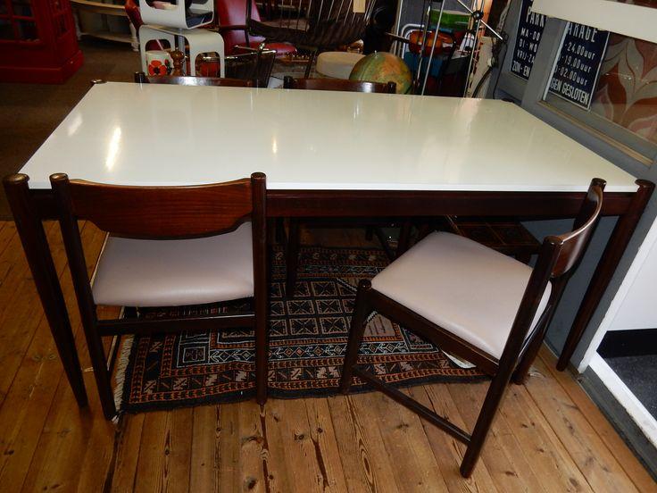 Retro, jaren 70, design tafel met wit blad en donkerbruine elegante poten. Het witte blad heeft een paar gebruikers vlekjes, maar verkeerd in goede staat. Afmetingen van de tafel zijn ongeveer 168 cm bij 88.5 cm breed en is 75 cm hoog. Bij de tafel staan vier bijpassende stoelen met skyledederen zitting(niet origineel). Afmeting stoel is ongeveer is ongeveer 47.5 cm breed, hoogste gedeelte is 78 cm en de zithoogte is 48 cm. Setprijs € 195,00.