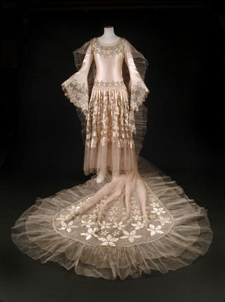 A wedding dress ensemble designed by Norman Hartnell. The dress was worn by Mrs Carl Bendix (nee Daisy Hancox) at the Dream of Fair Women Ball held in aid of the Winter Distress Fund at Claridges Hotel on 27 February 1928.