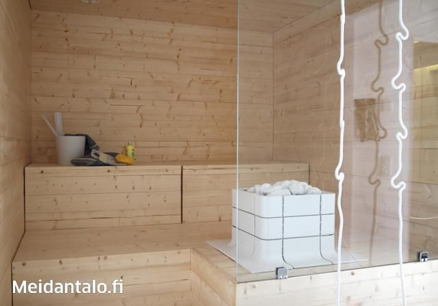 Vaalea sauna, jossa Tulikiven Nuoska-kiuas integroituna lauteisiin.