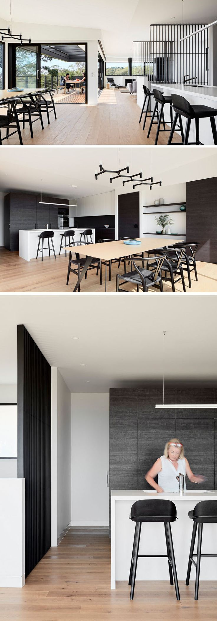 Beside the living area in this home is the indoor dining area and kitchen. In the dining room, the black chandelier matches the black chairs, while in the kitchen, a bright white kitchen island is a strong contrast against the dark wood cabinetry.
