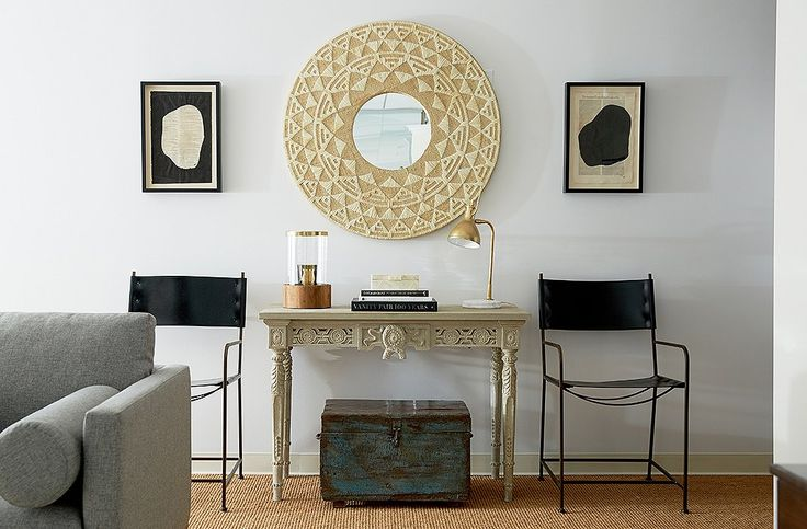 """Among Alex's favorite vignettes in The Studio is thishigh-contrast display arranged withblack leather-and-iron chairs, antique art, a raffia mirror, and an ornate carved console. """"It's wiping out a lot of color, but you're juxtaposing a lot of elements."""""""