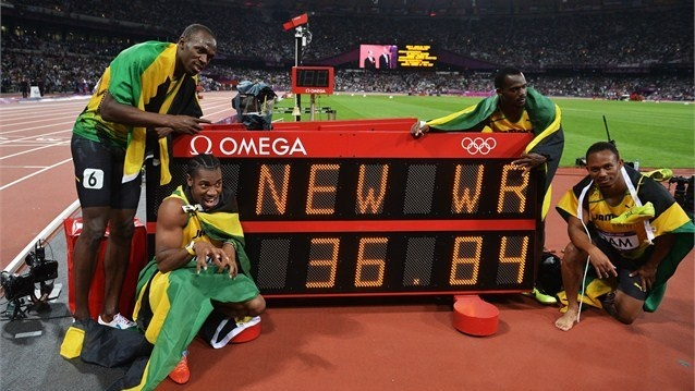Usain Bolt, Yohan Blake, Michael Frater and Nesta Carter of Jamaica celebrate next to the clock after winning gold and setting a new world record of 36.84 during the Men's 4 x 100m Relay Final on Day 15 of the London 2012 Olympic Games at Olympic Stadium