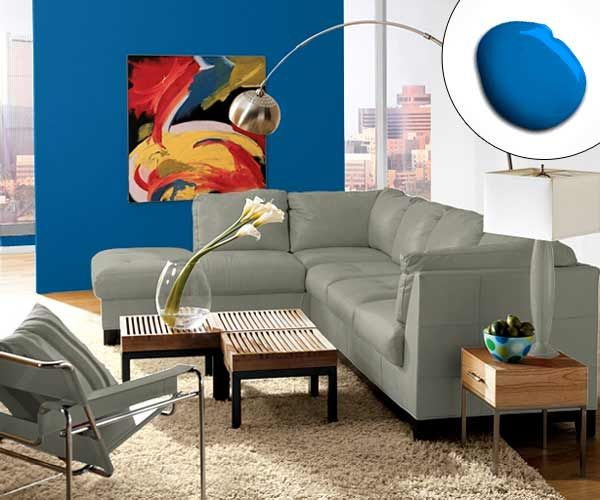 A colorful abstract painting—with a blue wall as an oversize frame—draws the focus in an otherwise-neutral living room. | Jay Blue SW 6797, @SherwinWilliams