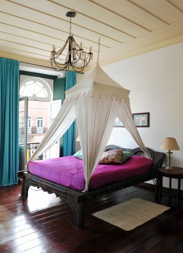 Carved Wood bed frame. canopy, and chandelier. Love the pop of color from the drapes and the bedding .