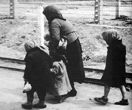 """Having gone through the selection process, a Jewish woman and her children walk to the gas chambers at Birkenau. Birkenau, part of the Auschwitz complex of camps (it was known as Auschwitz II) means """"Birch Wood"""", and was named for the birch forest surrounding it.  Unlike Auschwitz I, which was the main camp, and Auschwitz III, Monovitz, or Buna, a factory work camp, Birkenau was used solely for extermination and cremation of human beings.  I can think of few images more terrible than this."""