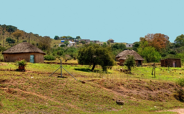 old zulu thatched huts on the outskirts of a village processed in hdr
