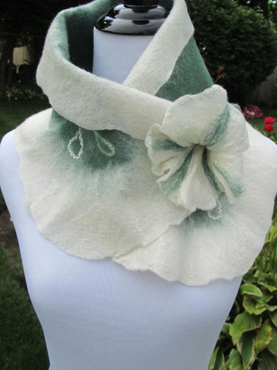 Felted Scarf creamy white and green with matching felted flower pin. Felt Wearable Art. Boho Accessory.     Crafted in fine merino wool and bamboo fibers, hand dyed and wet felted. This scarf is light and soft, comfortable and fun to wear. It measures 29 inches in length and 9 inches wide. Pretty forest shades of green and a flower pin complete this piece of wearable art.