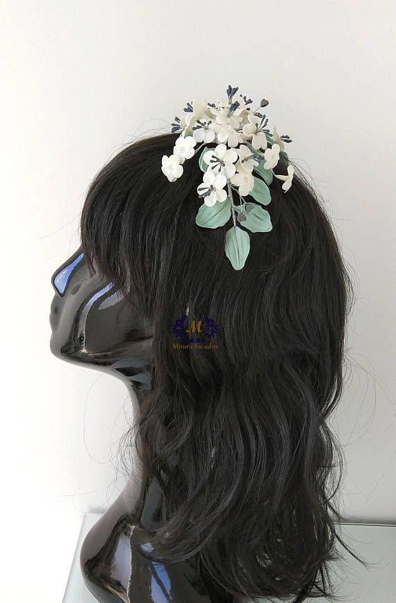 Precioso tocado con flores en blanco con el toque de los pistilos gris azulado, con hojas enverde olivo, y la nota romántica la ponen unos diminutos corazones en metal gris. Las flores están moldeadas en porcelana fría, con una elaboración minuciosa y detallada para darle un toque
