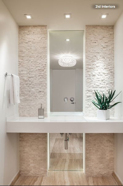 This sleek Miami powder room features a limestone mosaic wall, a faucet coming out from the mirror and a glamorous ceiling fixture. Light fixture: Caboche