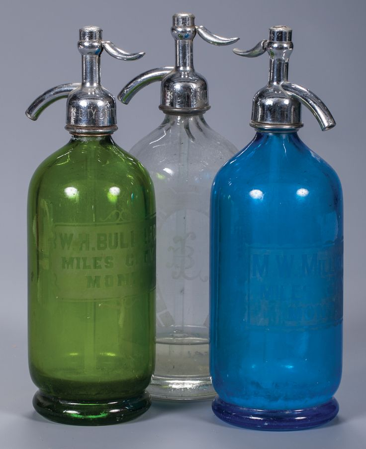"""Three Miles City, Montana Seltzer Bottles. All full size (11 1/2"""" tall) Etched glass bottles. a) Green, """"W H Bullard - Miles City Mont."""" with Miles City Bottling Works cap.  b) Blue, """"M W Milligan - Miles City Mont."""" with Coca Cola Bott Co. cap.  c) Clear, Louis Bach - Miles City Mont"""" in horseshoe with Miles City Bottling Works cap.  All 11 1/2"""" overall.  Provenance: From the Estate of Thomas W. Lorimer."""