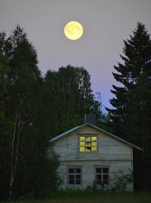 The last sunbeams reflects in the window of an abandon house, while a full moon lights up the night. Photographer Therese Henriksson, available as poster at printler.com, the marketplace for photo art.