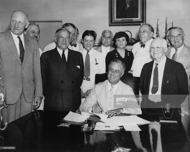 US President Franklin D. Roosevelt (1882 - 1945) signs the Social Security Act, 14th August 1935. From left to right, Robert Lee Doughton, chairman of the House Ways and Means Committee, Edwin E. Witte, Director of the President's Social Security Committee, with Senator Robert F. Wagner, co-author of the bill behind him, Senator Robert La Follette, Senator Augustine Lonergan, Labor Secretary Frances Perkins, Senator William H. King, Rep. David John Lewis, co-author of the bill and Senator…