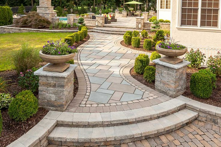 A winding path is clad with an artful mix of Monticello slabs in Azzurro, Rock Garden Brown, and Chocolate Brown colors, framed with a single band of Antika and further defined with a bolder Parisian paver in Chocolate Brown. This paver creates a heavier visual line to guide the eye along the twists and curves of the top-notch workmanship. www.techo-bloc.com, www.facebook.com/techobloc