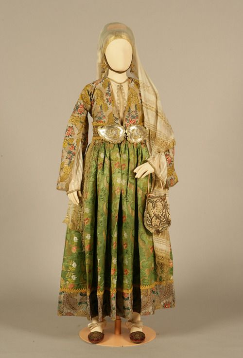 Old type bridal costume of Kymi, Evia (Euboea). 18th century. © Peloponnesian Folklore Foundation Collection, Nafplion. This bridal costume is a rarity. The dress is made of pure silk brocade imported from Western Europe, with a hem of a different brocade. The brocaded design of the hem is the same as that of the waistcoat but the material is of poorer quality, which reveals the existence of two kinds of material with the same woven design.