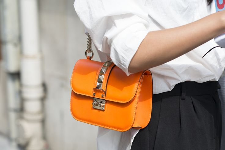 Orange handbags will liven up any monochrome or black-and-white look #popofcolor #Valentino #rockstuds