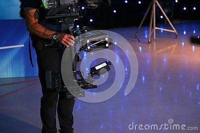 Man using a steadicam in a television studio - specific equipment to stabilize the camcorder.