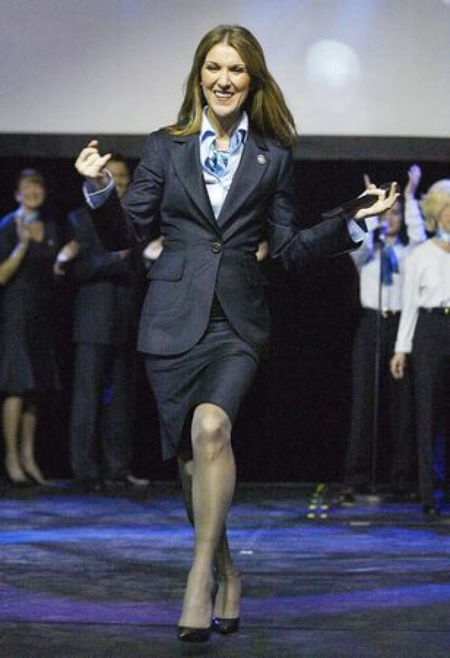 Celine Dion, wearing the new Air Canada flight attendant uniform, performs for employees at the airline's headquarters in Montreal on Tuesday, Oct. 19, 2004. The airline, which emerged from creditor protection last month, held the party for employees to show off its new uniforms and livery for its planes. (AP PHOTO/Ryan Remiorz)
