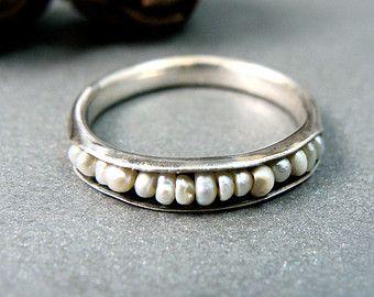 Perlas de agua dulce grises delicados son acunadas en los pliegues de este anillo de plata esterlina. Las perlas se llevan a cabo firmemente en lugar por un alambre de plata. El interior del anillo ha sido oxidado por contraste y para dar un aspecto más orgánico. Este anillo es más 1/8 de ancho y 1/8 de alto. Esta banda orgánica fue cuidadosamente hechos a mano por mí y se ve muy solo o con otros anillos de pila. Usted puede elegir la opción de que el canal donde las perlas se fijan...
