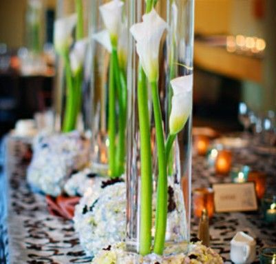 The guestbook table will feature a tall cylinder vase filled with submerged white calla lilies with crystals in the base.