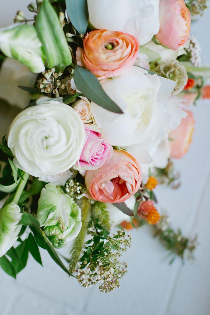 detail of loose bridal bouquet of white peony, white ranunculus, rosita vendela roses, spirea, white majolik spray roses, bunny tail grass, peach ranunculus, scabiosa pods, white parrot tulips & greenery.
